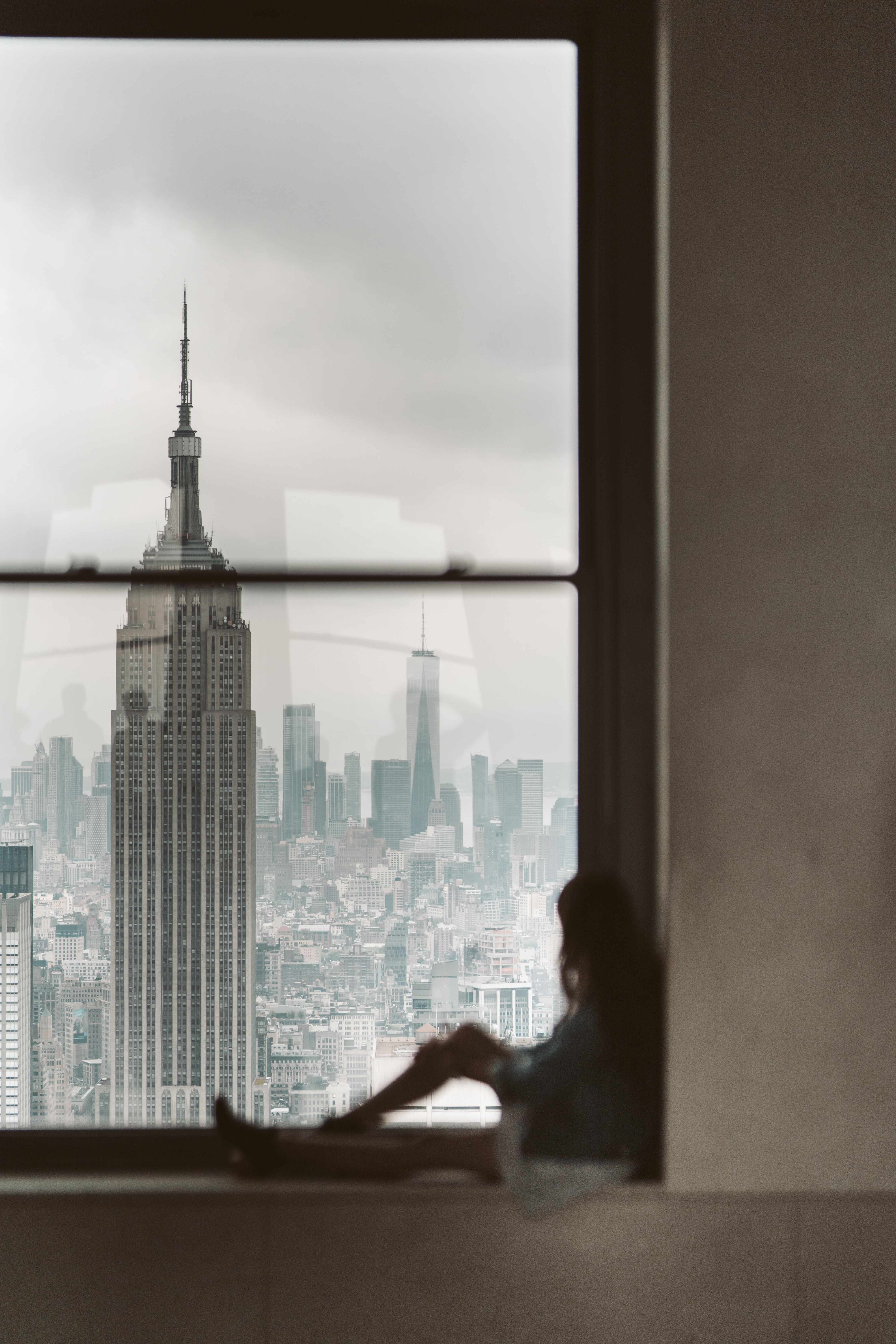 woman-sitting-at-window-sill-looking-out-the-window-at-new-3889873
